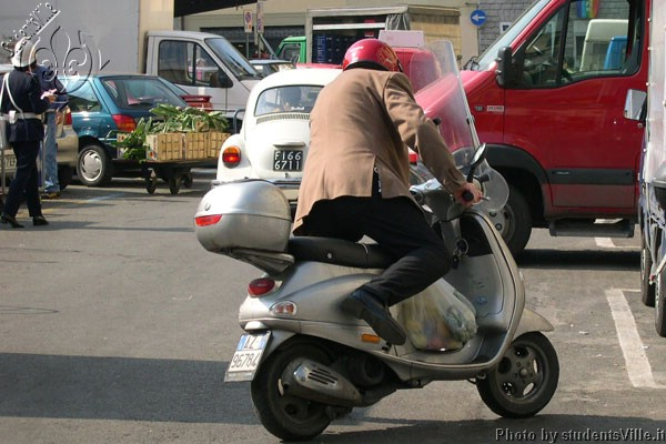 Vespa shopping (600Wx400H) - Jumping on the Vespa after the daily shopping at the market. It's by now lunch time! (Photo by Marco De La Pierre)